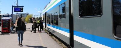 Ett tåg har stannat vid perrongen i Grankulla. Människor stiger på tåget.