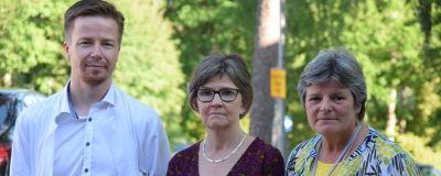 En man och två kvinnor poserar framför kameran. Mannen är klädd i vit läkarrock.