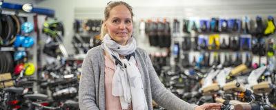 En kvinna står mitt bland cyklar i en sportaffär. Hon ser glad ut