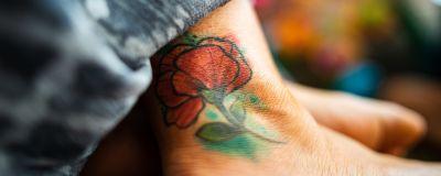 En färgglad tatuering av en blomma på en fot.