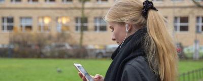 Hanna Ylöstalo lyssnar på ljudbok via sina hörlurar.