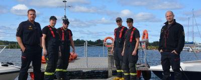 Sex stycken brandmän står på en brygga vid vattnet.
