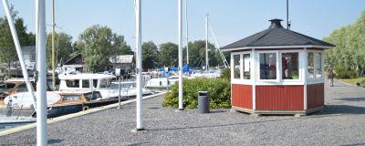 litet hus och båtar i hamn