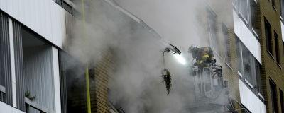 Brandman i skylift spanar in i ett brinnande hus.