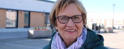 En kvinna med kort ljust hår och en lila scarf runt halsen.