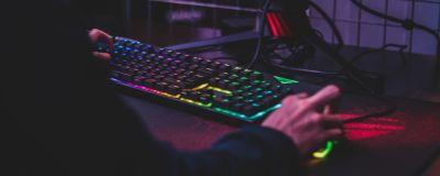 En pojke sitter i ett mörkt rum vid en dator med neonlysande tangentbord och mus.