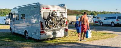 En husbil på en camping. Lättklädda semesterfirare går förbi.