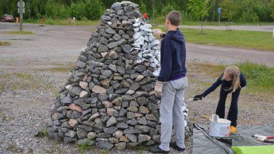 barn målar ett kummel av sten på västra åstranden i borgå