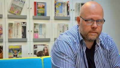 Joakim Bonns på Yle Österbottens redaktion. Bakom honom finns en hylla med tidningar.