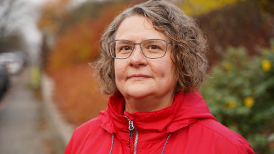 En fet äldre kvinna med kort grått hår och glasögon iklädd röd jacka tittar in kameran. I bakgrunden syns höstfärger.