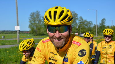 Kristian Kylén, en man med solglasögon, skäggstubb, gul cykelhjälm och gul skjorta, ler mot kameran.
