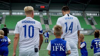 Vi ser Janne Grönroos och Tim Sparv bakifrån i blå-vita fotbollsskjortor med efternamnen på ryggen. Några fotbollsjuniorer i Vasa IFK-spelarskjortor syns i bildens nedre kant.