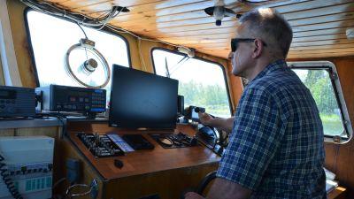En man styr en båt.