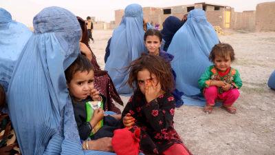 Flyktingar, kvinnor i Burka och deras barn, sitter på sanden i staden Herat.