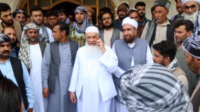 Muhammad Ismail Khan, klädd i helvitt, omringad av sina anhängare vid hans hus i Herat.