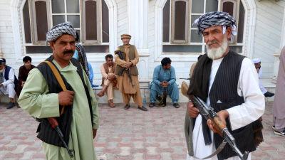 Två män med stormgevär står och vaktar krigsherren Muhammad Ismail Khans hus i Herat.