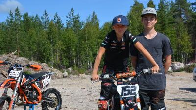 Två unga motocrossförarare står bredvid varandra.