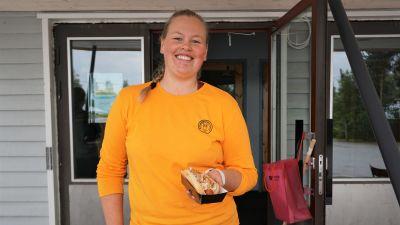 Kvinna i gul tröja står med en hotdog i handen.