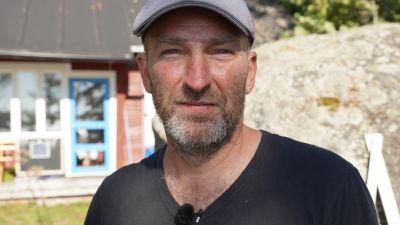 Ett porträtt av en medelålders man med gråsprängt skägg och grå keps på huvudet.