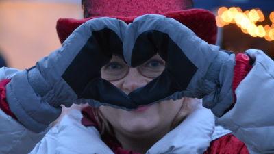 Kvinna med röd sammetshatt står och håller händerna som ett hjärta framför sitt ansikte.