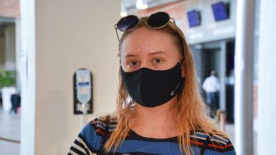 Silja Järvinen med solglasögon på huvudet och svart munnskydd inomhus.