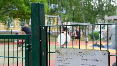 Muminparken i Borgå stadsparken. I bilden syns parkens gröna staket och i bakgrunden barn som leker.