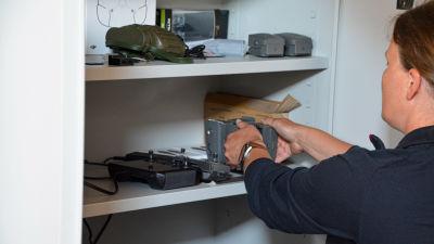 Drönarutrustning i ett vitt skåp. En person håller på att lyfta fram en del av utrustningen.