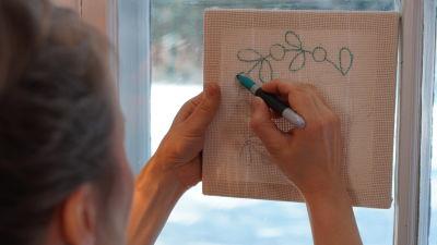En hand ritar av mönster på tyg på en tavla som hålls upp mot ett fönster