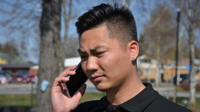 Ung man med vietnamesiskt ursprung i telefon