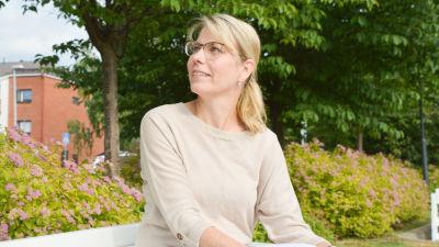 Johanna Tamminen sitter på en bänk i en park i beige tröija.