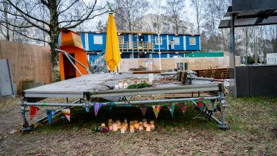 Kynttilöitä ja kukkia Koskelan murhapaikalla. Taustalla rakennustyömaan parakit.