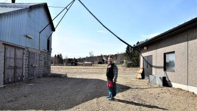 en konstnär pekar på en sladd som hänger från ett hus