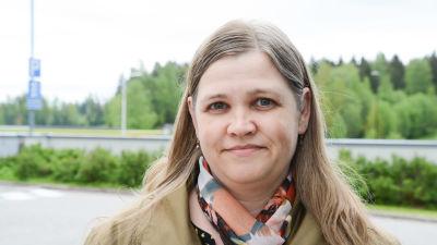 Tuija Nygård utomhus med en färggrann skarf runt halsen.
