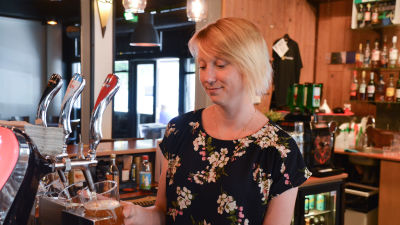 Nora Heikkilä fyller på öl i ett stop på pubben för Hotelli Zilton.