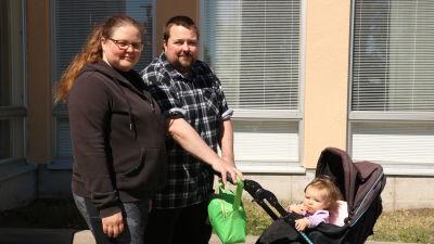 En man och en kvinna står vid en barnvagn. I barnvagnen sitter en flicka.