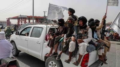 Joukko taliban-taistelijoita valkoisen avolava-auton lavalla 17. elokuuta 2021.