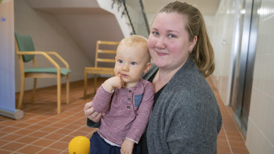 Anna Lindgren sitter med sin son på golvet. Hon tittar in i kameran.