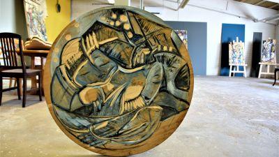 en atelje med ett runt konstverk snidet i trä i förgrunden