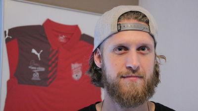 En man med keps på huvudet och långt hår och skägg. Bakom honom syns en röd skjorta upphängd på väggen.
