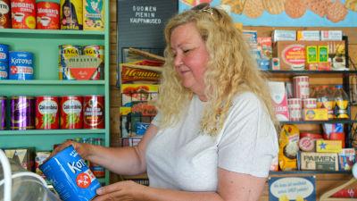Minna Järvinen i en 50-60-tals butiksmiljö håller upp en konservburk.