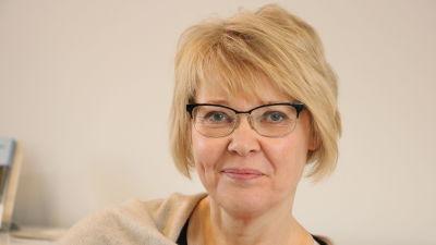 En kvinna med kort blont hår och glasögon.