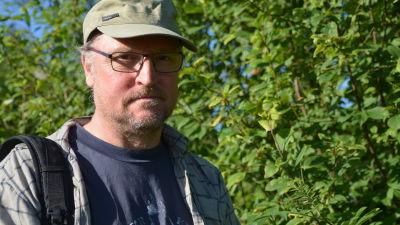 En man med glasögon och skärmmössa, på ena axeln en ryggsäck. Häggbuskage i bakgrunden.