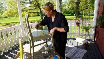 En kvinna målar en stol.