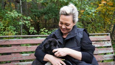 Maria Wright istuu ulkopenkillä Bobbie-koiranpentu kainalossaan.