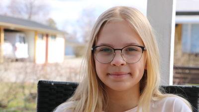 En elvaårig flicka med långt blont hår och glasögon sitter ute på en stol.