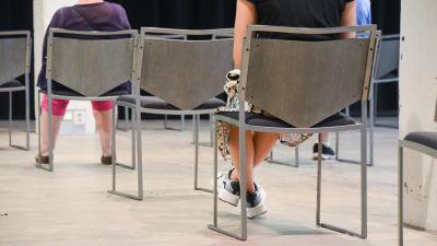 Två personer sitter med ryggen mot på stolar som är placerade i en rad i ett stort rum.