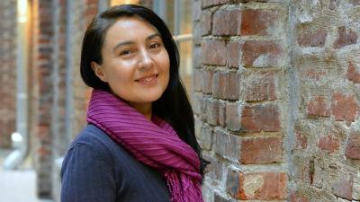 En kvinna med mörkt hår står invid en tegelvägg och ler mot kameran.