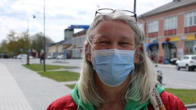 En kvinna med långt grått hår med munskydd framför ansiktet.