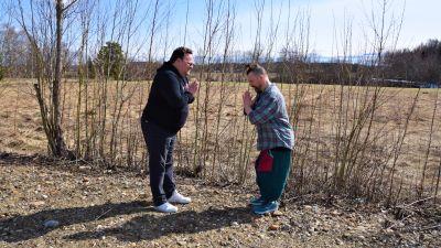 två män bugar artigt mot varandra vid en åker