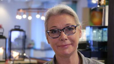 En kvinna med glasögon står bakom disken på en restaurang.